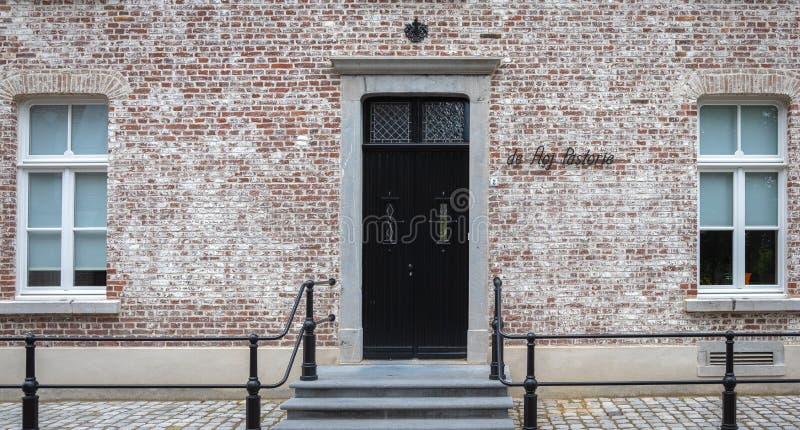 Ein altes Tor und Fenster auf der Fassade einer alten, englischen Steinmauer stockbild
