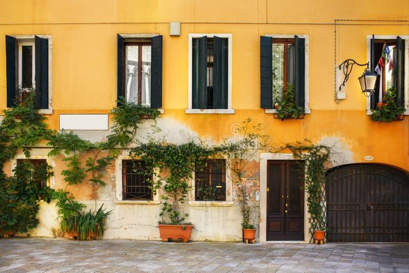 Ein altes Venician-Haus mit Fenstern, Anlagen und einer Tür lizenzfreies stockfoto