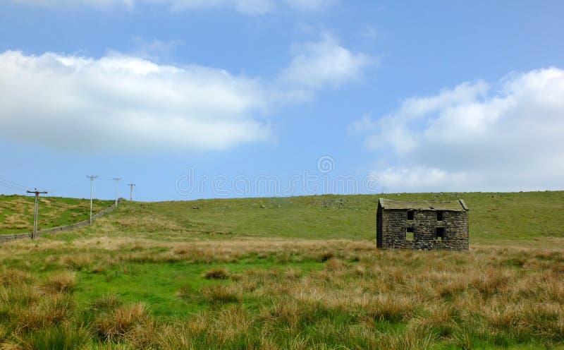 Ein altes verlassenes Steinbauernhaus in der grünen Weide auf hohem Penninheidemoor mit hellem blauem Himmel stockbild