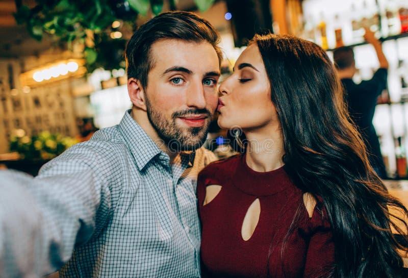 Ein anderes selfie von Paaren Mädchen küsst ihren Partner, während er ein Foto macht Sie schauen zusammen glücklich lizenzfreies stockbild