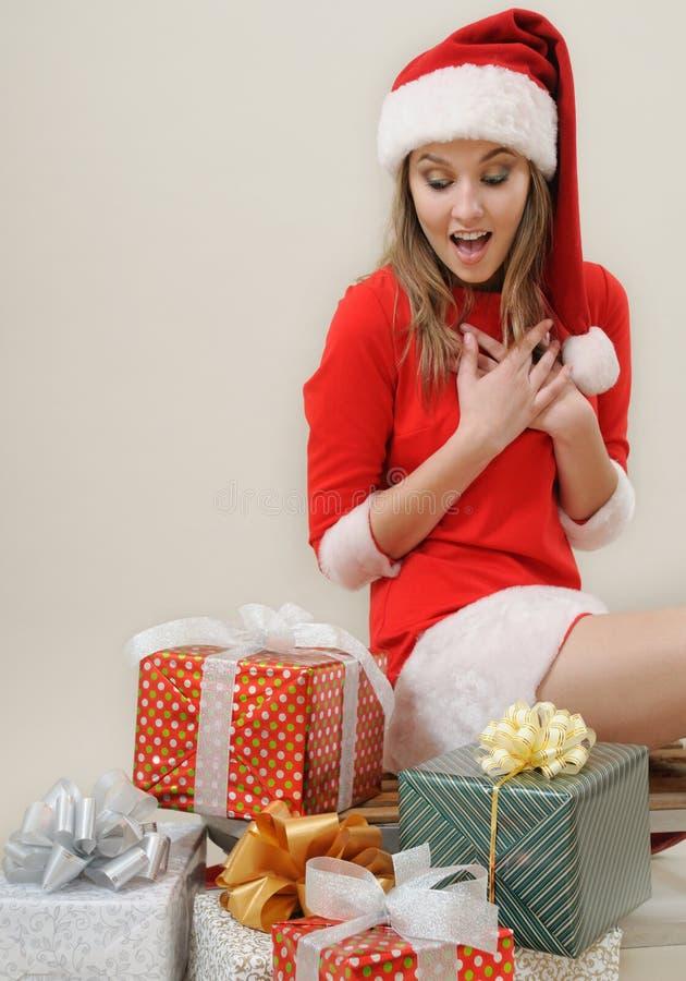 Ein angenehmes Überraschungsmädchen in Sankt-Hut mit Geschenken für Weihnachten lizenzfreie stockbilder