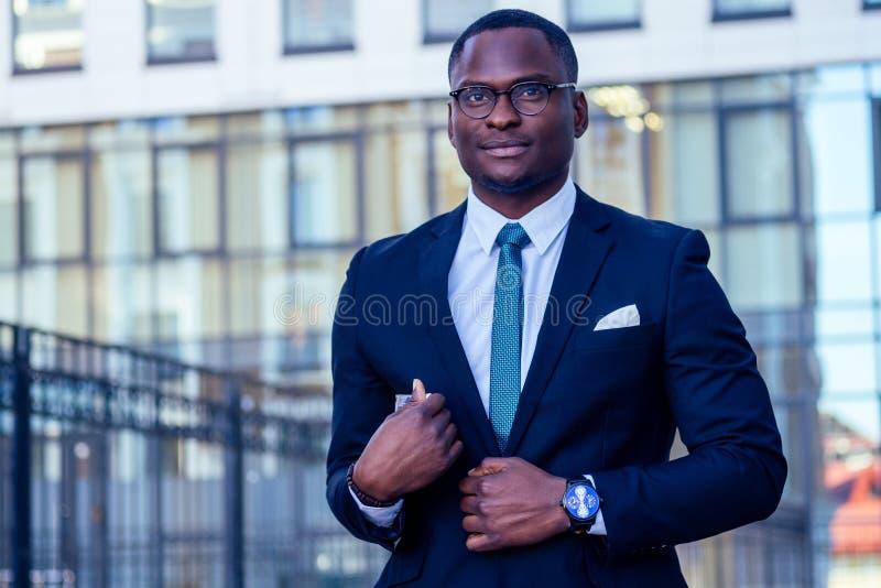 Ein ansprechender und stilvoller afro-amerikanischer Geschäftsmann in einer modischen Jacke und einem weißen Hemd mit einem Krage stockfoto