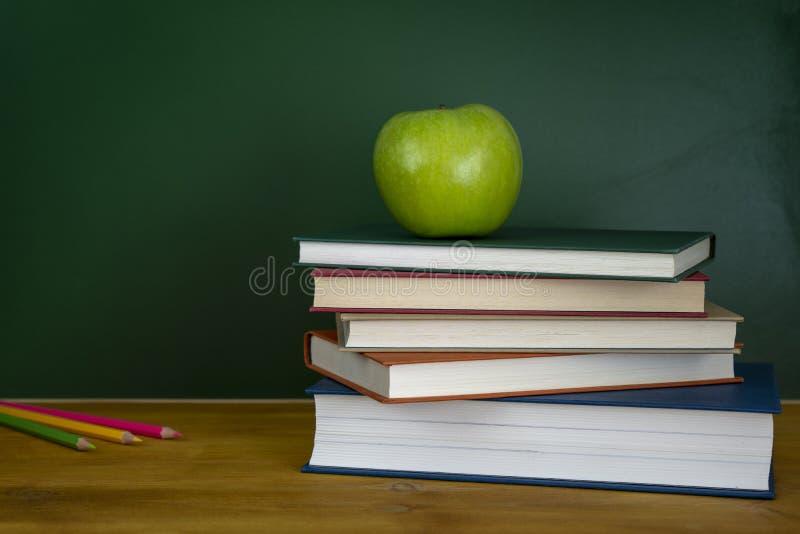 Ein Apfel oben auf einen Stapel der Bücher Leere Tafel auf der Rückseite lizenzfreie stockbilder