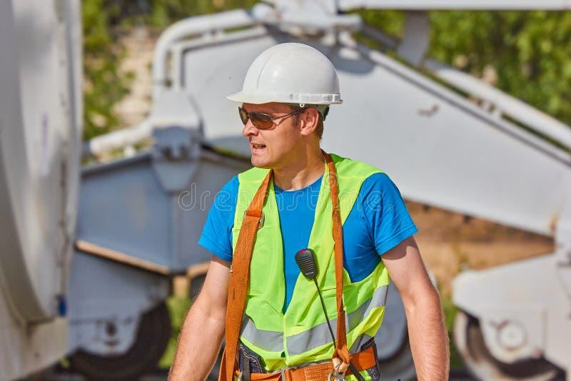 Ein Arbeiter in einer Sonnenbrille, ein weißer Helm, ein heller Westen blickt zur Seite stockfoto