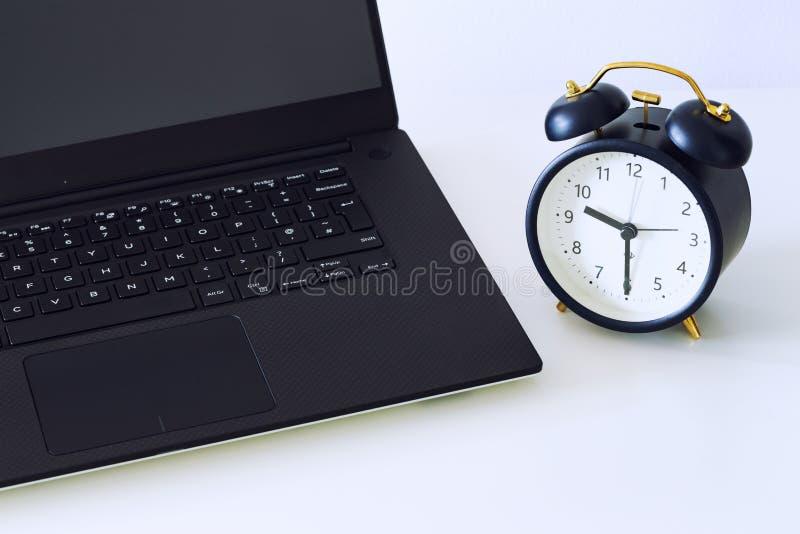Ein Arbeitsschreibtisch mit einem Computer und Bürozusätzen und ein Wecker, der die Zeit weg läuft misst Das Konzept des dringend lizenzfreie stockfotos