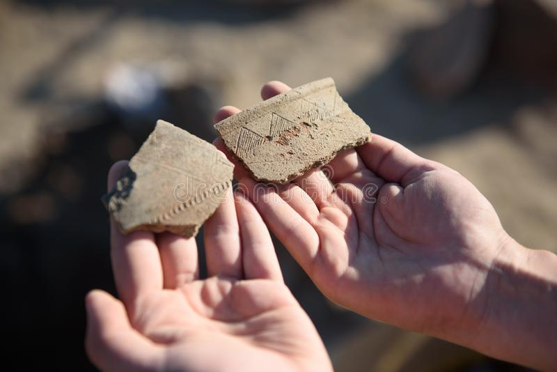 Ein Archäologe an einer archäologischen Fundstätte zeigt Fragmente stockfoto