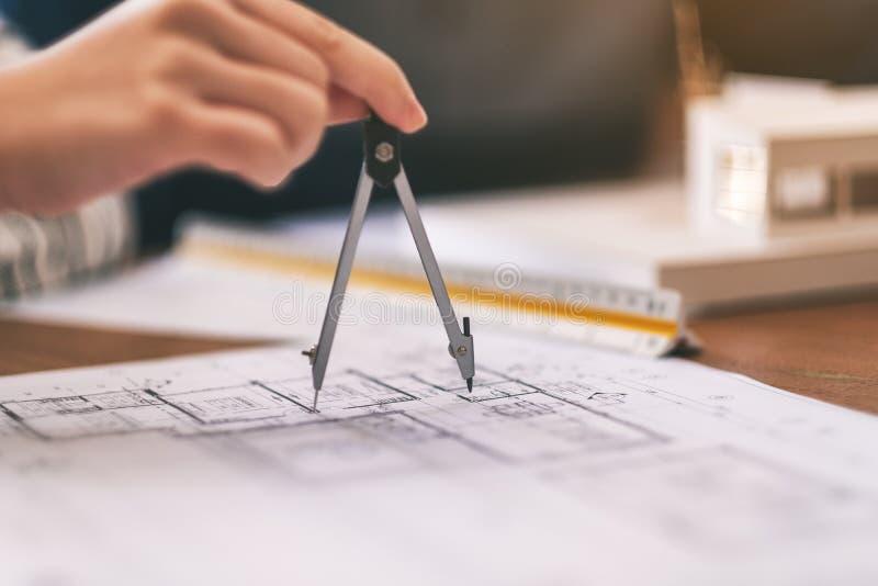 Ein Architekt, der Kompass verwendet, um Geschäftszeichnung zu zeichnen und zu messen stockbild