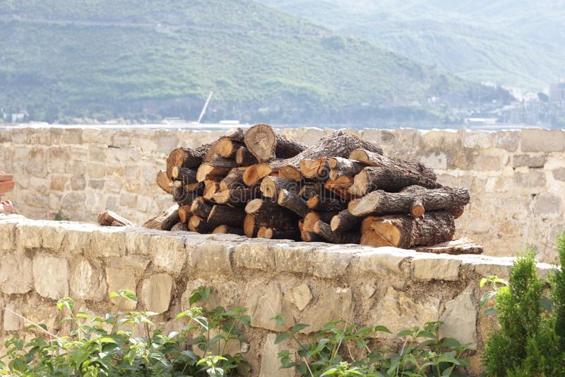 Ein Arm voll Brennholz auf einem Steinregal an einem sonnigen Tag unter den Bergen stockbilder