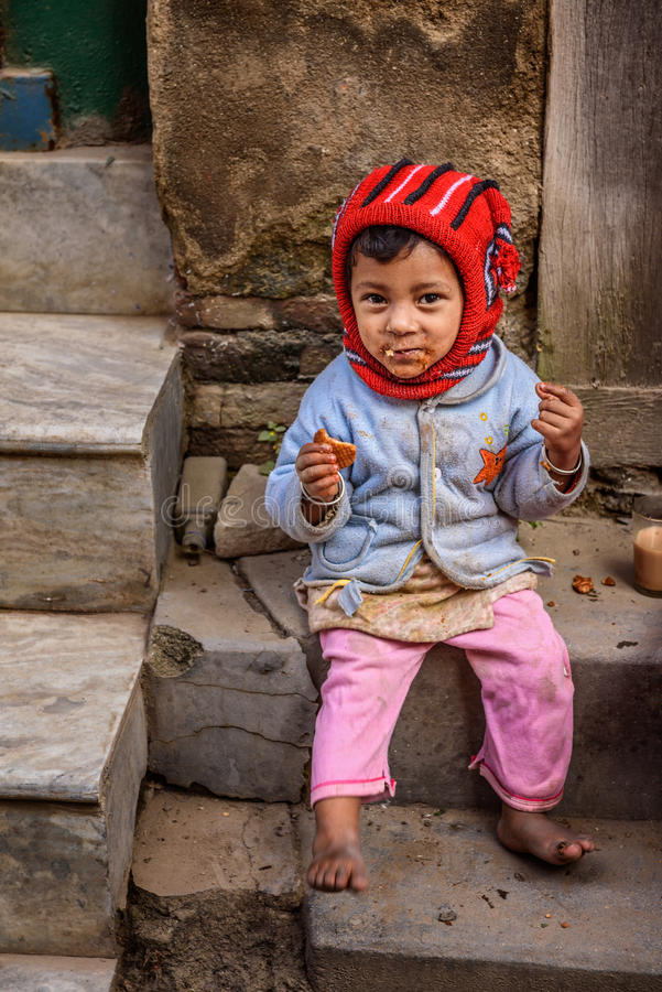Ein armes Mädchen in Nepal einen Cracker in der Straße von Kathmandu essend lizenzfreie stockfotos