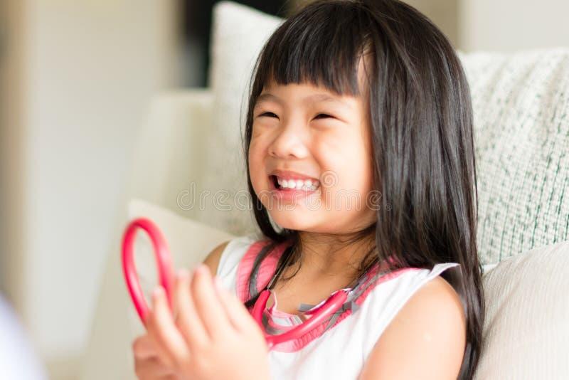 Ein asiatischer Blick des kleinen Mädchens bequem wenn Doktor, der durch u überprüft stockbilder