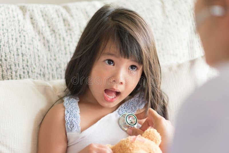 Ein asiatischer Blick des kleinen Mädchens erschrocken wenn Doktor, der durch die Anwendung überprüft lizenzfreie stockfotos