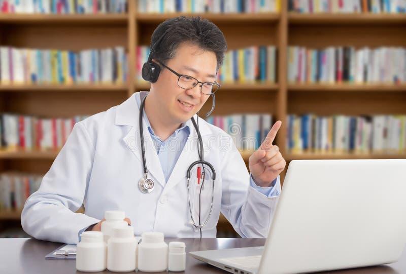 Ein asiatischer Doktor, der sich entfernt mit einem Patienten berät Telehealth-Konzept lizenzfreies stockbild