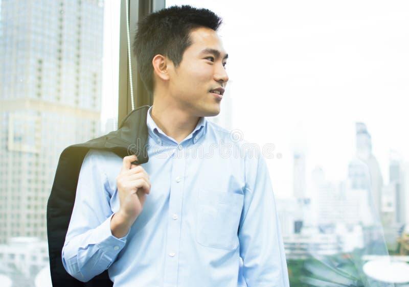 Ein asiatischer Geschäftsmann steht neben dem Fenster mit Stadtansicht lizenzfreies stockfoto