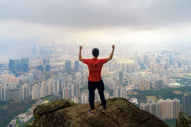 Ein asiatischer touristischer Mann, der Stadt auf Felsen, Gebirgshügel in Hong Kong-Stadtzentrum im Abenteuerkonzept während der  lizenzfreie stockfotos