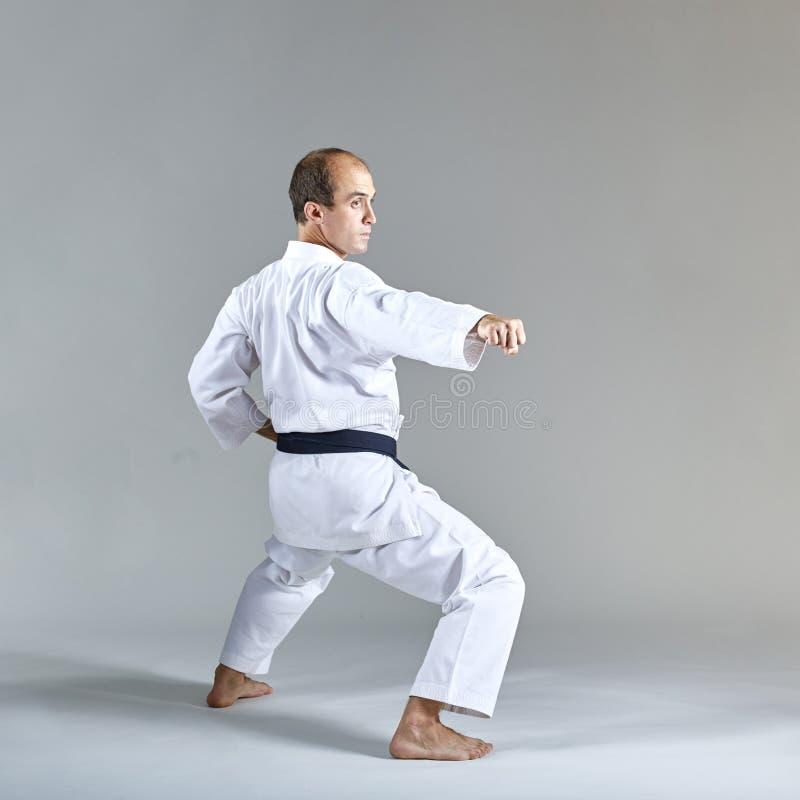 Ein Athlet bildet einen Durchschlag in einer formalen Karateübung gegen einen grauen Hintergrund aus stockfotos