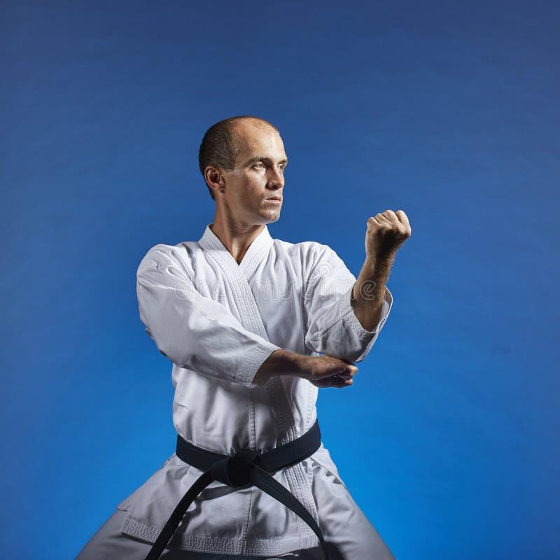 Ein Athlet führt formale Übungen von Karate auf einem blauen Hintergrund durch stockfotos