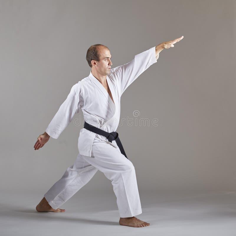 Ein Athlet mit einem schwarzen Gürtel und im karategi tut formale Karateübungen stockbilder