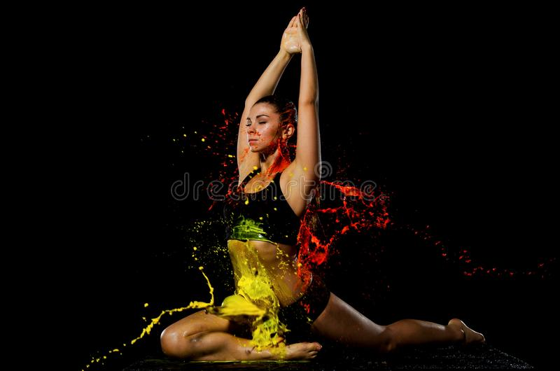 Ein athletisches Mädchen, das in der gelben und orange Farbe gebadet wird, nimmt an Yoga teil lizenzfreie stockbilder
