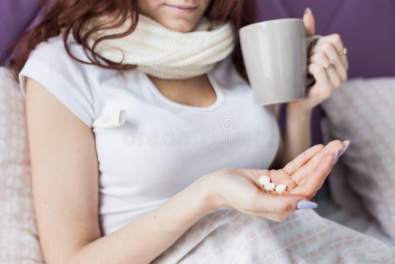 Ein attraktiver junger Brunette mit dem braunen Haar sitzt in ihrem Bett mit einem Becher und Pillen K?lten und Hauptbehandlung lizenzfreie stockfotografie