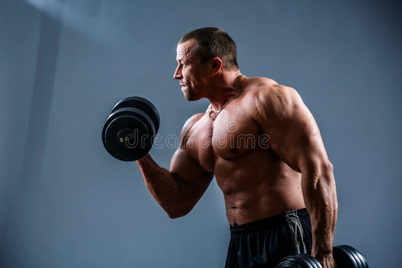 Ein attraktiver muskulöser Kerl, der mit Gewichten ausarbeitet stockbild