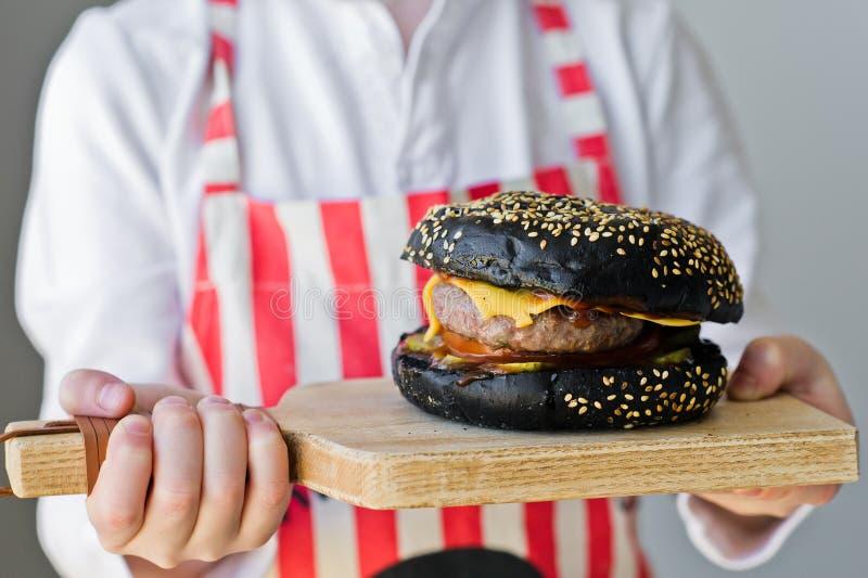 Ein attraktiver rothaariger Junge h?lt ein h?lzernes hackendes Brett mit einem Hamburger Rezept f?r das Kochen des schwarzen chee stockbilder