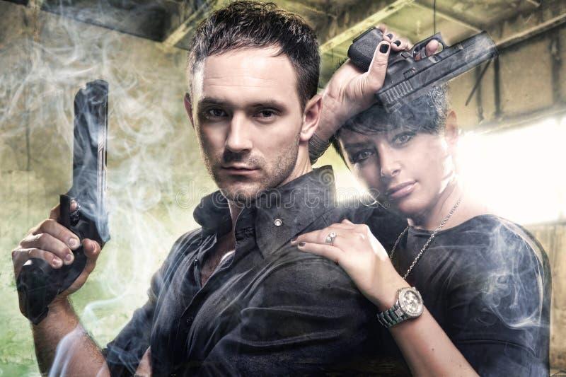 Ein attraktives junges Paar mit Gewehren stockfoto