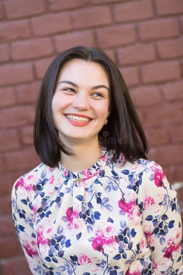 Ein attraktives Mädchen, das vor dem hintergrund einer Backsteinmauer lächelt lizenzfreies stockbild