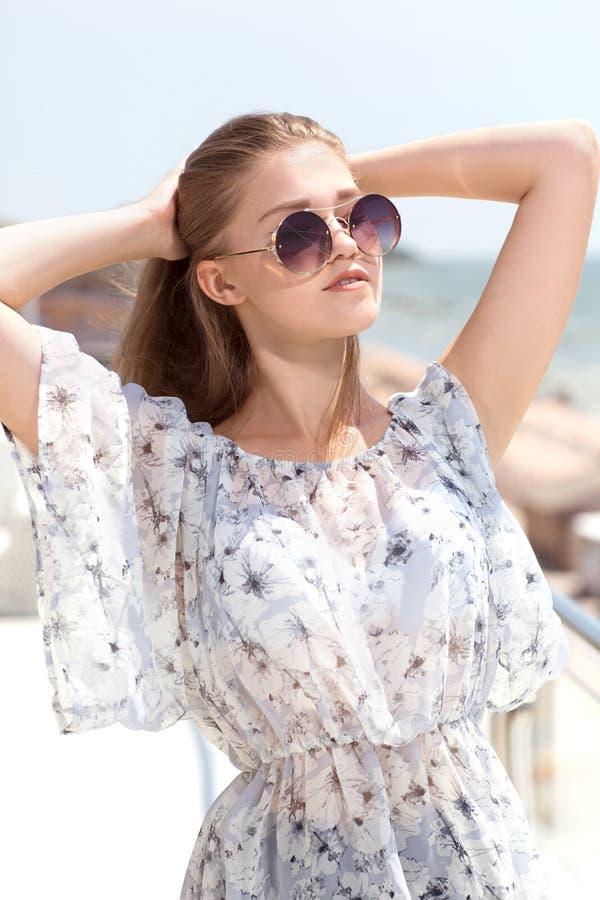 Ein attraktives Mädchen in Sonnenbrillen auf einem Hintergrund des blauen Himmels Eine schöne junge Frau in einer hellen Bluse au lizenzfreies stockbild
