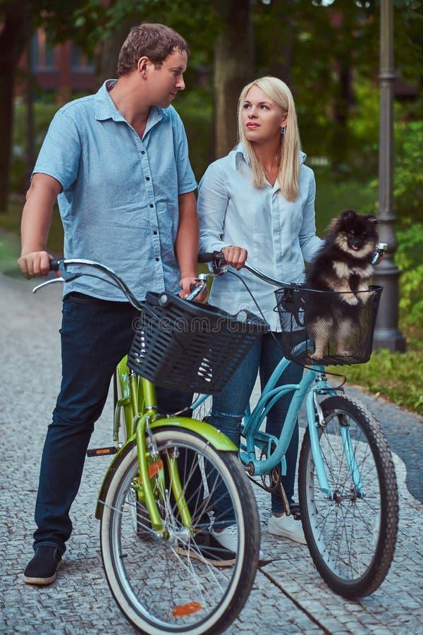 Ein attraktives Paar einer blonden Frau und des Mannes kleidete in der zufälligen Kleidung auf einer Fahrradfahrt mit ihrem nette lizenzfreies stockfoto
