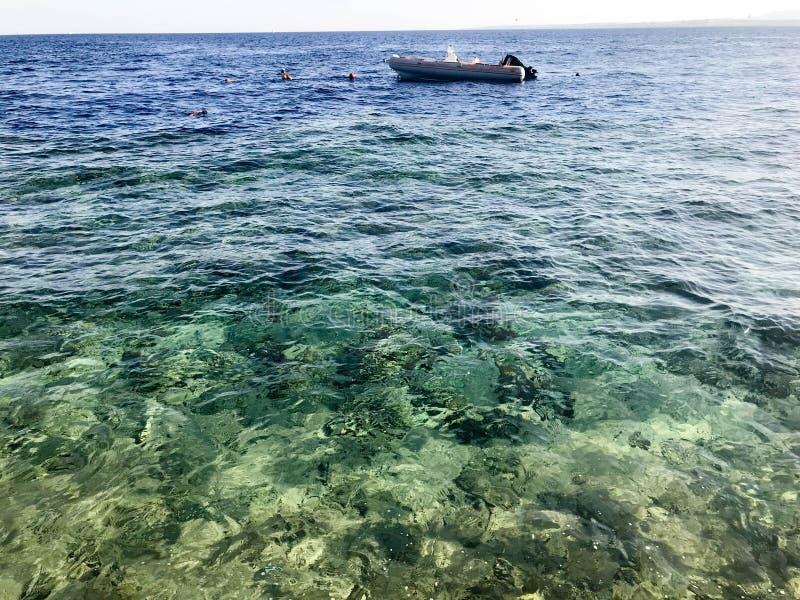 Ein aufblasbares Boot, ein Boot auf dem Hintergrund eines schönen sandigen Steinstrandes, Land, Strand und blaues Wasser, das Mee lizenzfreies stockbild