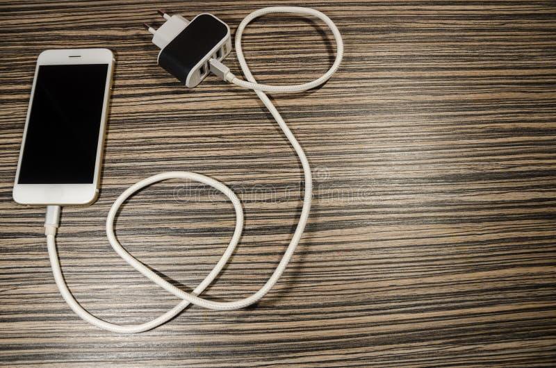Ein Aufladungstelefon angeschlossen mit Adapterblock durch Kabel stockbilder