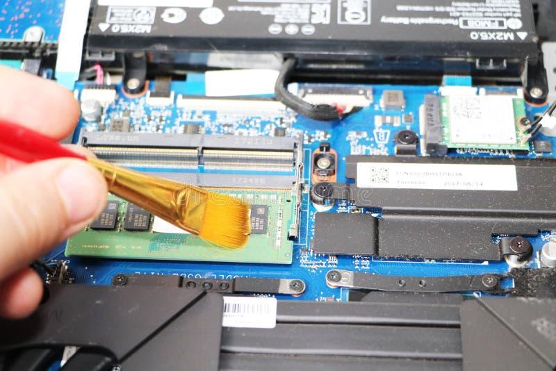 Ein Aussenseiter säubert eine Laptopkühlvorrichtung Verseuchtes Kühlsystem des Computers stockfotografie