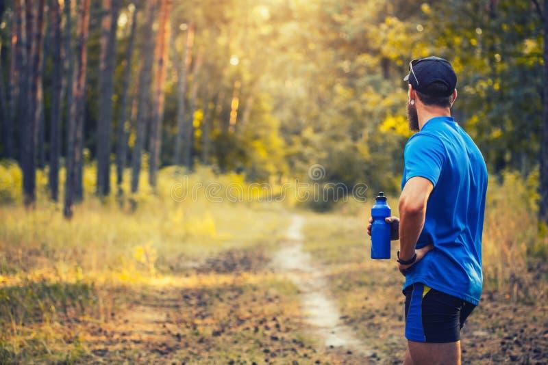 Ein bärtiger Athlet bereitet sich für einen Morgen vor, der entlang einen malerischen Waldweg laufen gelassen wird lizenzfreies stockbild