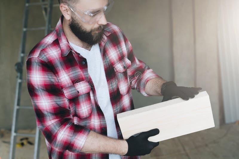 Ein bärtiger Hippie-Tischler des jungen Mannes steht in der Werkstatt, hält eine hölzerne Stange in seinen Händen, betrachtet sie stockbilder