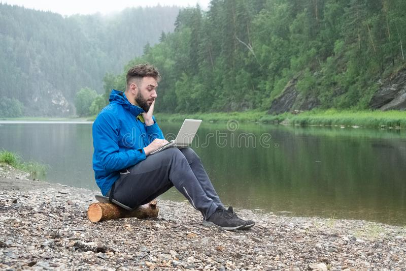 Ein bärtiger junger Mann betrachtet in der Überraschung dem Schirm eines wasserdichten Computers Ein Kerl in einem Matrosen sitzt lizenzfreie stockfotografie
