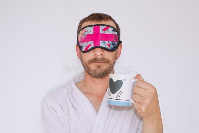 Ein bärtiger Mann in einem Hausmantel und eine Maske auf seinen Augen, einen Becher in seinen Händen halten Er trinkt Kaffee, um  stockfoto