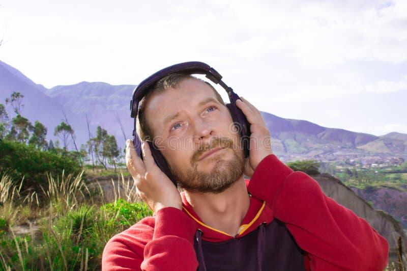 Ein bärtiger Mann hört Musik auf Kopfhörern, in der Natur stockbild
