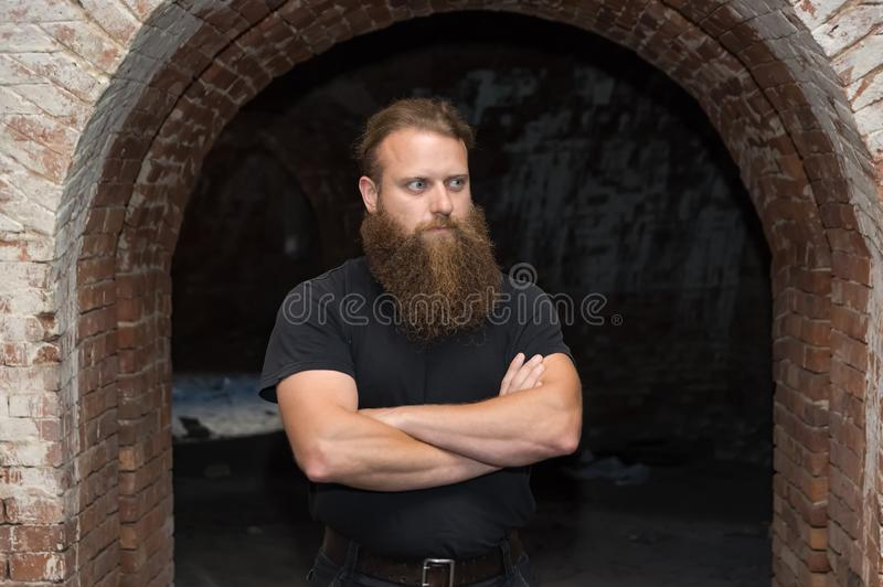 Ein bärtiger Mann mit den Armen gekreuzt, Stände in einem düsteren Raum unter einem gebogenen Bogen lizenzfreie stockfotografie
