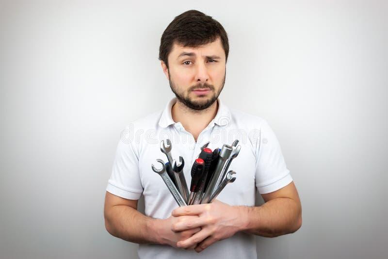 Ein bärtiger Mann mit verengt einem Auge mit einem Blumenstrauß von Schlüsseln und von Schraubenziehern stockfotos