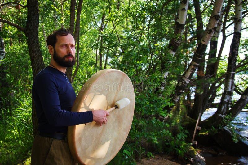 Ein bärtiger Mann spielt Trommeln im Waldemotionalen meditierenden Lebensstil Entspannende Selbstbeobachtung stockfotografie