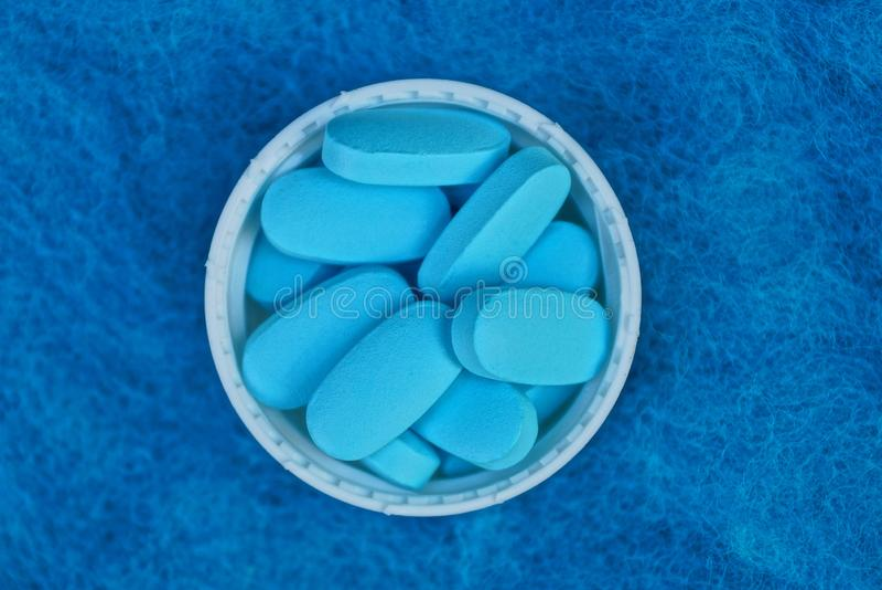 Ein Bündel blaue Pillen in einer weißen Flaschenkapsel auf einem woolen Stoff stockbild