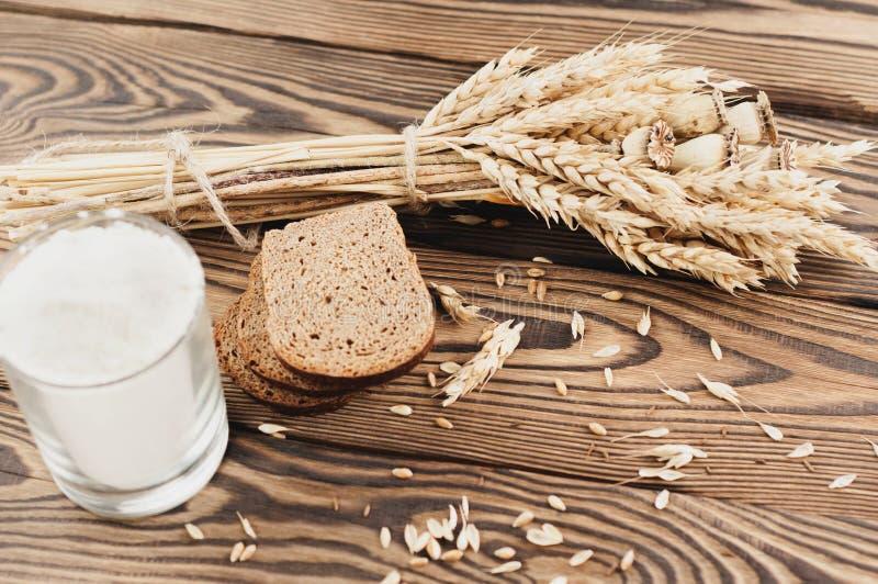 Ein Bündel des Weizens und der Mohnblume und Los zerstreutes Korn und drei Scheiben brot und Mehl im Glas auf alten hölzernen Pla stockfoto