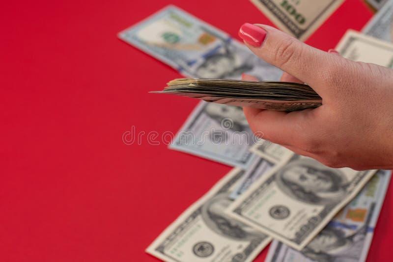 Ein Bündel Geld in einer weiblichen Hand mit roten Nägeln, Habsucht für Geld, hundert Vorderseite der Dollarscheine, altes Hunder lizenzfreies stockfoto