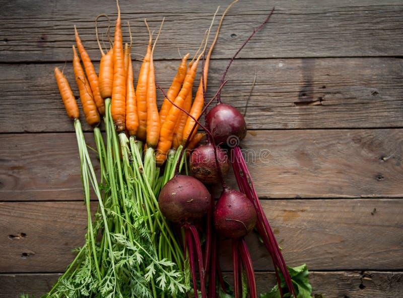 Ein Bündel Karotten und Rote-Bete-Wurzeln Frische Karotten, Rote-Bete-Wurzeln Haufen mit grünen Stämmen Rohe Karotten und Rote-Be lizenzfreies stockfoto