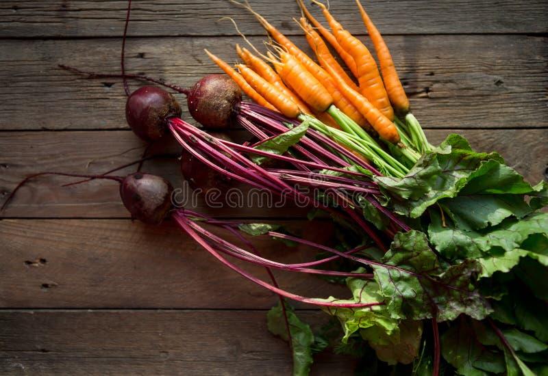 Ein Bündel Karotten und Rote-Bete-Wurzeln Frische Karotten, Rote-Bete-Wurzeln Haufen mit grünen Stämmen Rohe Karotten und Rote-Be stockfoto