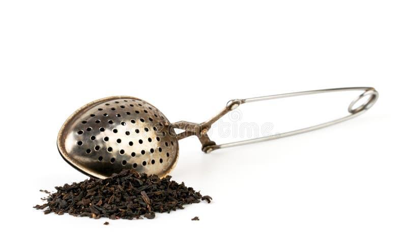 Ein Bündel von schwarzen Teeblättern und von Teelöffel auf einem weißen Hintergrund Getrennt stockfotografie