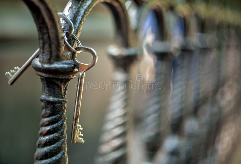 Ein Bündel von zwei Metallalten Weinlese-Türschlüsseln, die an einem Gusseisenzaun des künstlerischen Castings in einem Park mit  stockfotos