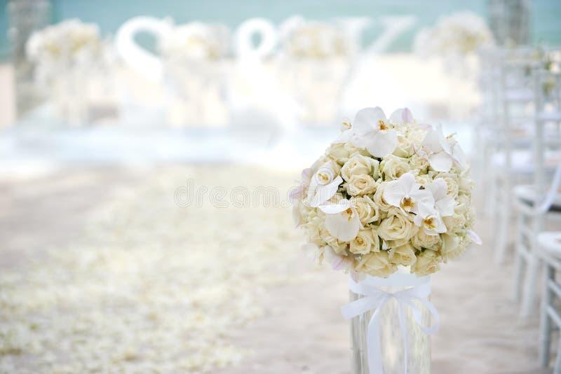 Ein Bündel weiße Sahnerosen, Orchideen auf dem Glasvase neben dem Gang an der Strandhochzeitszeremonie - oben geschlossen lizenzfreie stockfotos