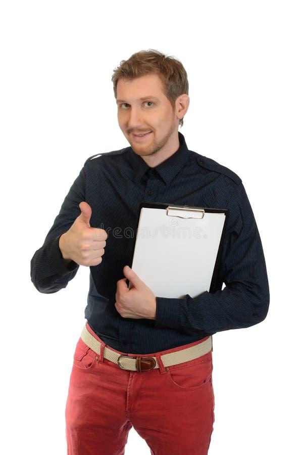 Ein Büroangestellter mit dem roten Haar stellt dar, dass Daumen herauf und in die andere Hand einen Ordner hält stockbilder