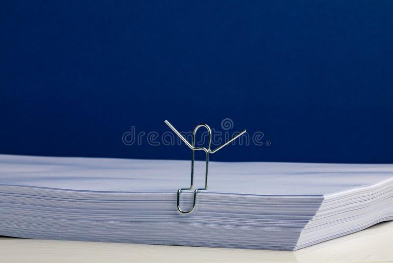 Ein Büroklammer-Charakter-Händchenhalten oben auf Paket Papier stockfotografie
